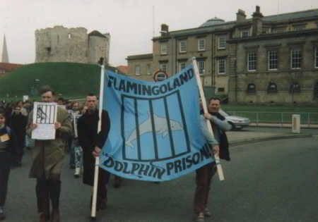 people holding banner - flamingoland dolphin prison